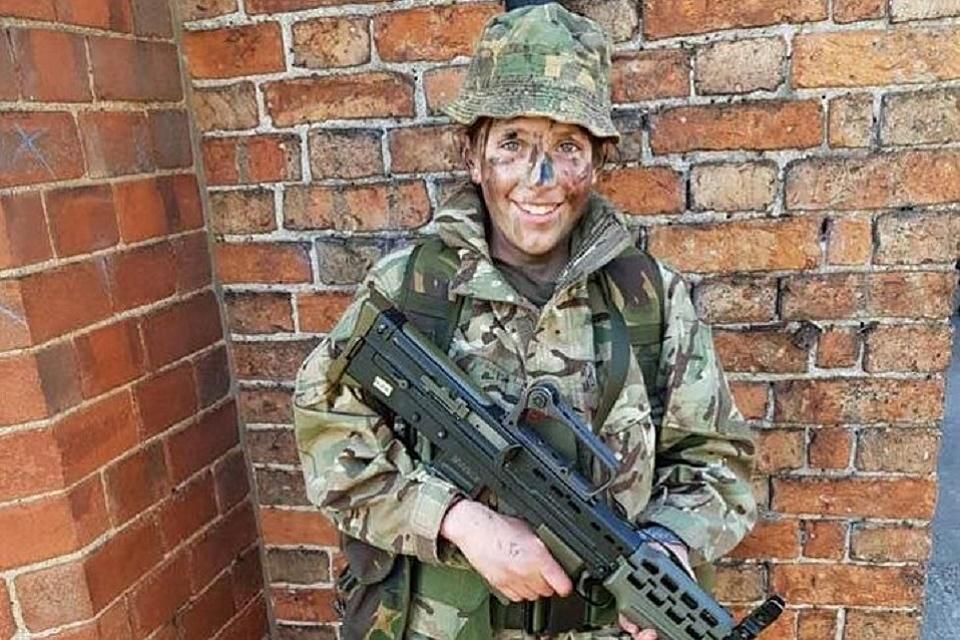 Cerys in camo uniform holding a large gun.