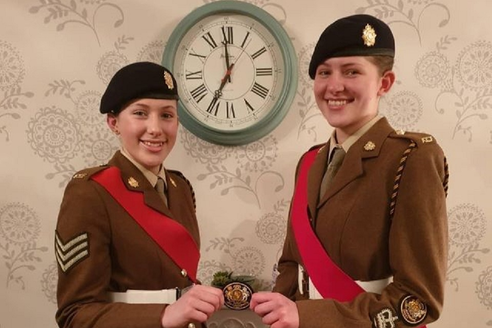 Cerys and Tegan in uniform holding an award.