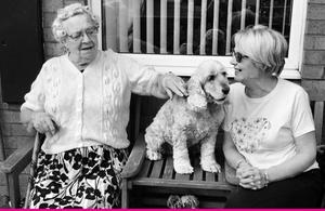 Черно-белое изображение двух человек, сидящих на скамейке, с собакой посередине.