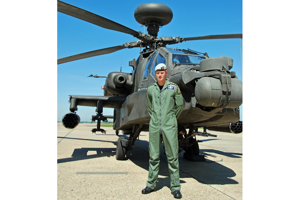 Captain Harry Wales standing in front of a British Army Apache attack helicopter