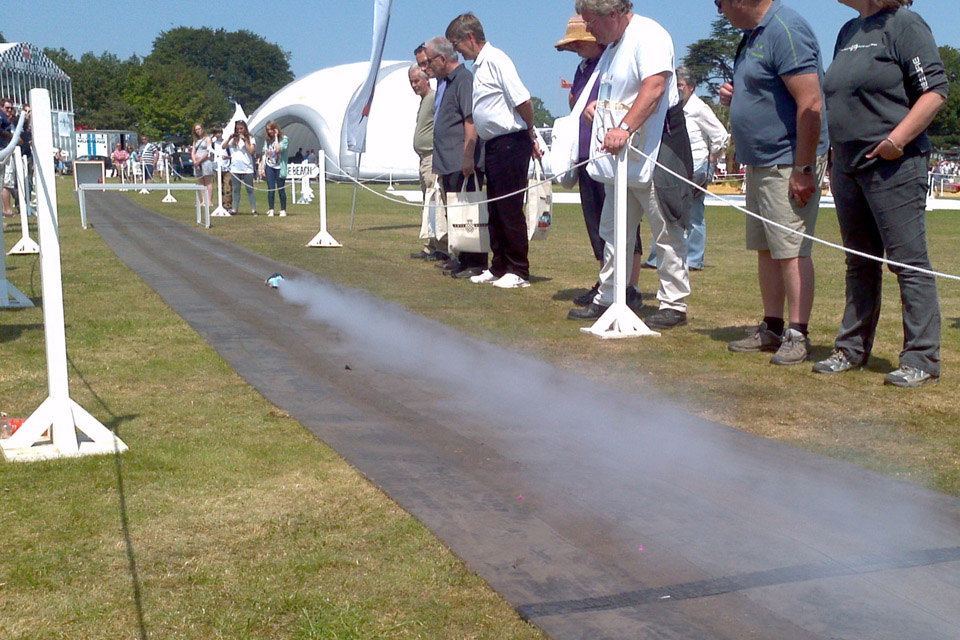 Spectators watch a rocket-propelled car on a track