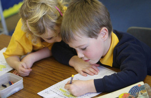Two primary school children working at their desks.