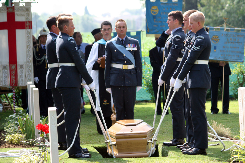 Members of the Queen's Colour Squadron lower the coffin into the grave