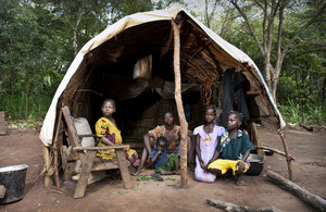 A family sit in a makeshift shelter in a forest clearing