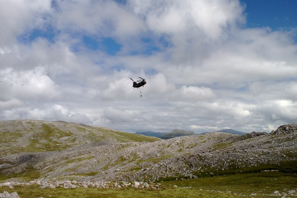 The RAF Chinook approaches the burial site