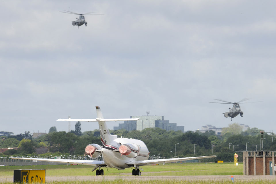 Two Royal Navy Sea King helicopters landing at RAF Northolt with a civilian aircraft in the foreground