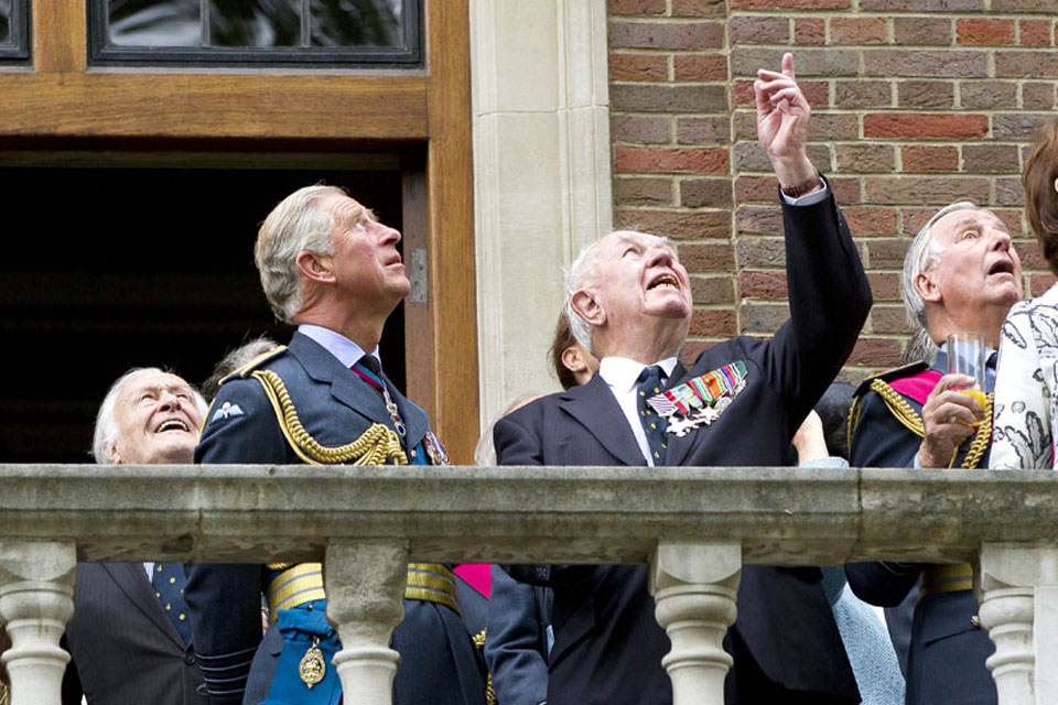 The Prince of Wales enjoying the flypast by the Battle of Britain Memorial Flight with veterans on the balcony of Church House
