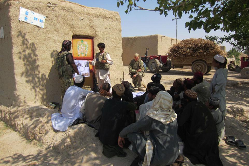 Afghan paramedic vet Jama Gul talking to local farmers about animal husbandry