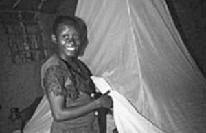A pregnant Kenyan woman prepares to climb under an insecticide-treated bednet