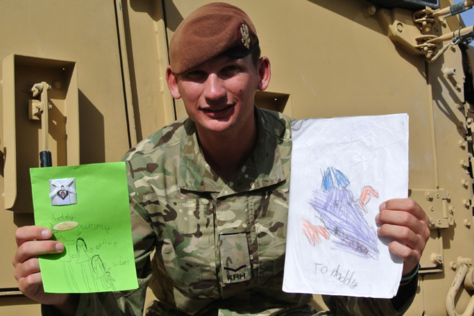 Lance Corporal Thomas Cook with Father's Day cards from his wife, Lucy, and two children