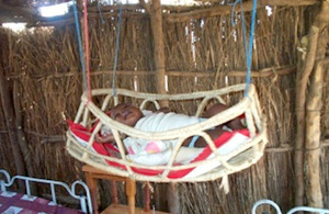 Baby in cradle moved away from smoke in Sudan