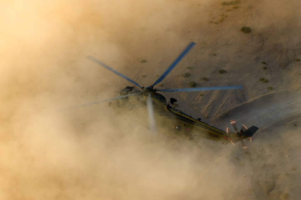 A Sea King helicopter practises landing in a dust cloud