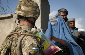 A British soldier hands a bag of rice to an Afghan woman at the Khuja Rawash Secondary School in Kabul