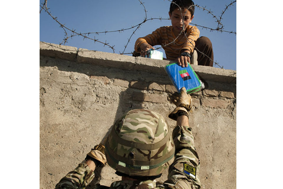 Major Kev Read of 16 Signal Regiment hands a pencil case to a child