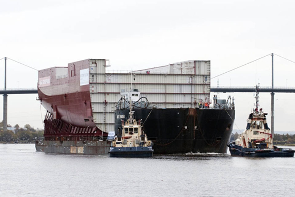 Lower Block 04 being transported on a large seagoing barge under the Erskine Bridge