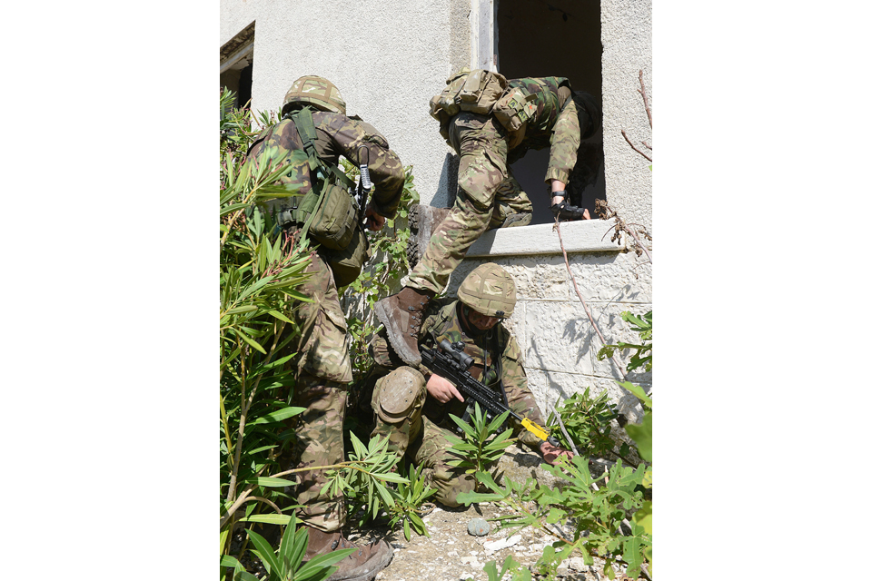 Royal Marines enter a building through a window