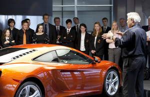 Man talking to young people and teachers around a McLaren car
