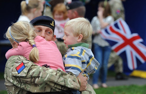 A soldier from the 19th Regiment Royal Artillery holds his children