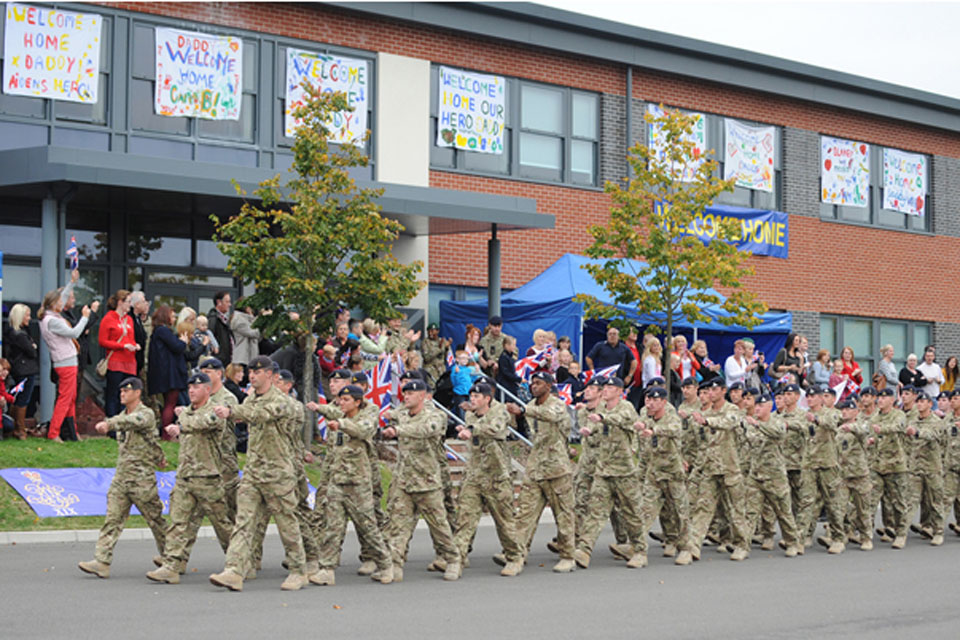 Families and loved ones cheer soldiers of the 19th Regiment Royal Artillery march into their barracks at Tidworth