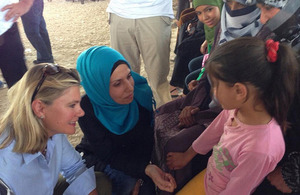 Photograph of Justine Greening talking to a refugee child in Jordan