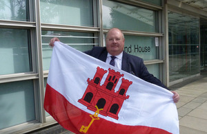 Eric Pickles with the Flag of Gibraltar outside the Department for Communities and Local Government.