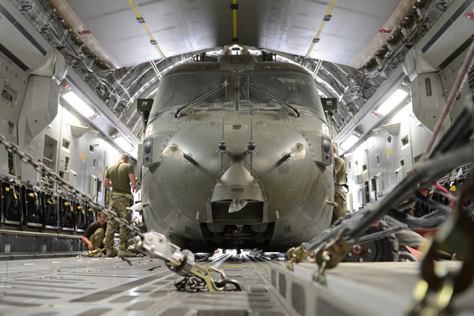 A Merlin helicopter is packed and secured into an RAF C-17 Globemaster transport aircraft