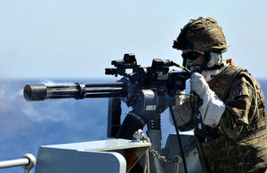 A sailor onboard HMS Sutherland conducts live firing off Gibraltar