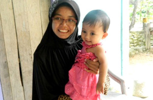 Project worker Intan with Santi's baby daughter Cerah Kamila.