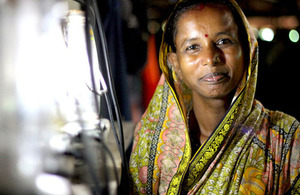 Picture of woman in India next to solar lantern