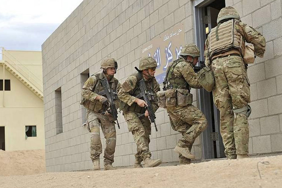 Royal Marines commandos enter a compound at the US Marine Corps Air Ground Combat Center, also known as Twentynine Palms, in California