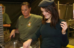 Sophie McShera, kitchen maid Daisy in the series Downton Abbey, serves up in the RAF field kitchen