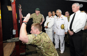 Commodore Bushnak (centre, in white, with moustache) views weapons training in the simulator at HMS Raleigh