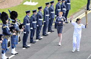 Sandie Kennedy carries the Olympic Torch past RAF Leuchars Main Gate