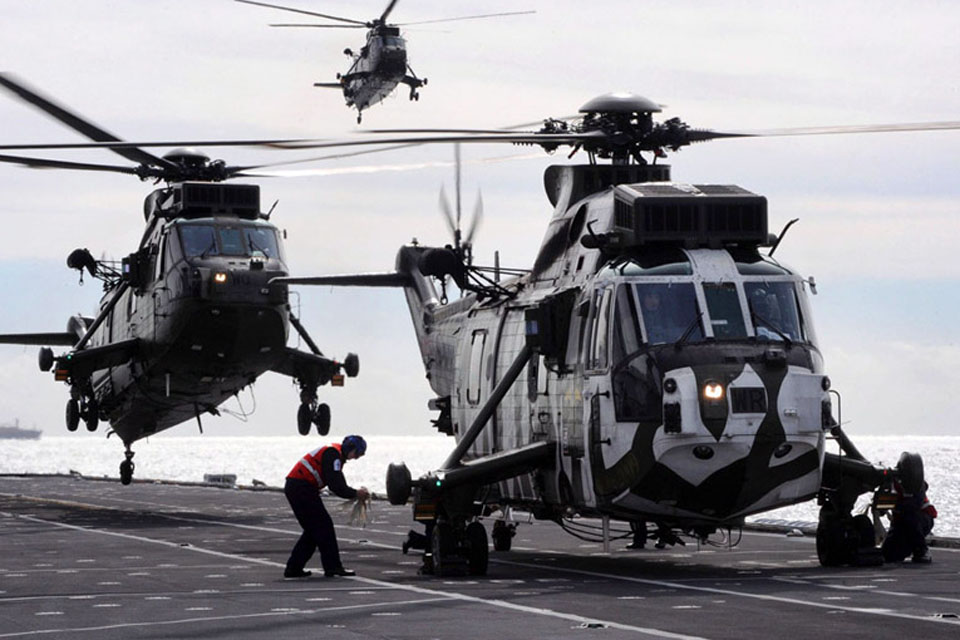 Three Sea Kings are recovered to the deck of HMS Illustrious