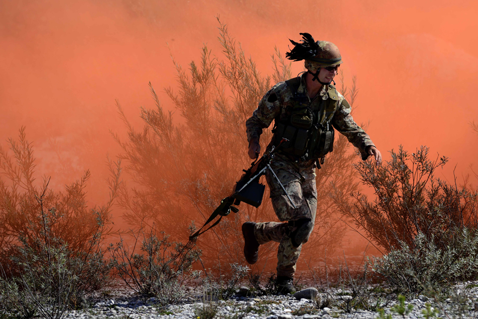An Italian soldier runs in front of concealing coloured smoke