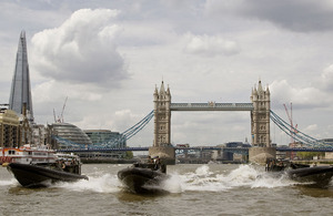 Royal Marines from 539 Assault Squadron prepare for their role in the Diamond Jubilee celebrations in offshore raiding craft on the River Thames with Tower Bridge and the Shard in the background