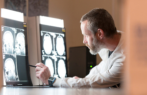 Alzheimer's researcher examining brain scans - courtesy of Alzheimer's Research UK