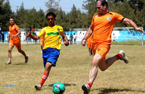 The 'Helmand Olympics' football competition between Afghan and British forces (playing in orange) at the Karzai Stadium in Lashkar Gah