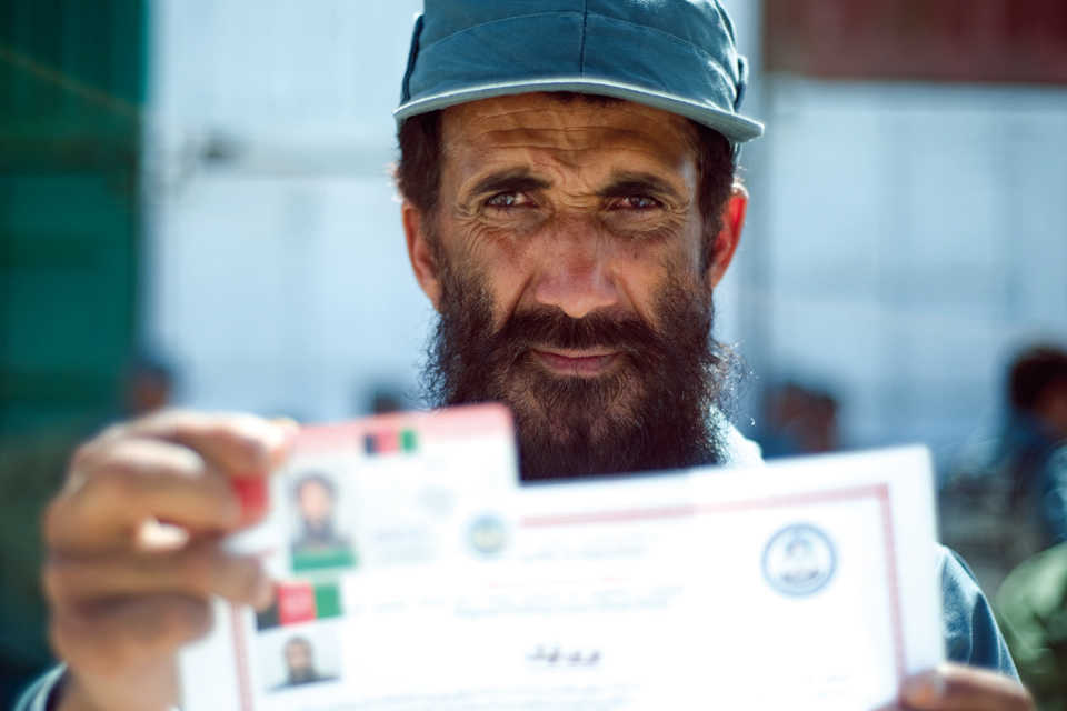 An officer from the Afghan Uniform Police proudly holds up his certificate and ID card