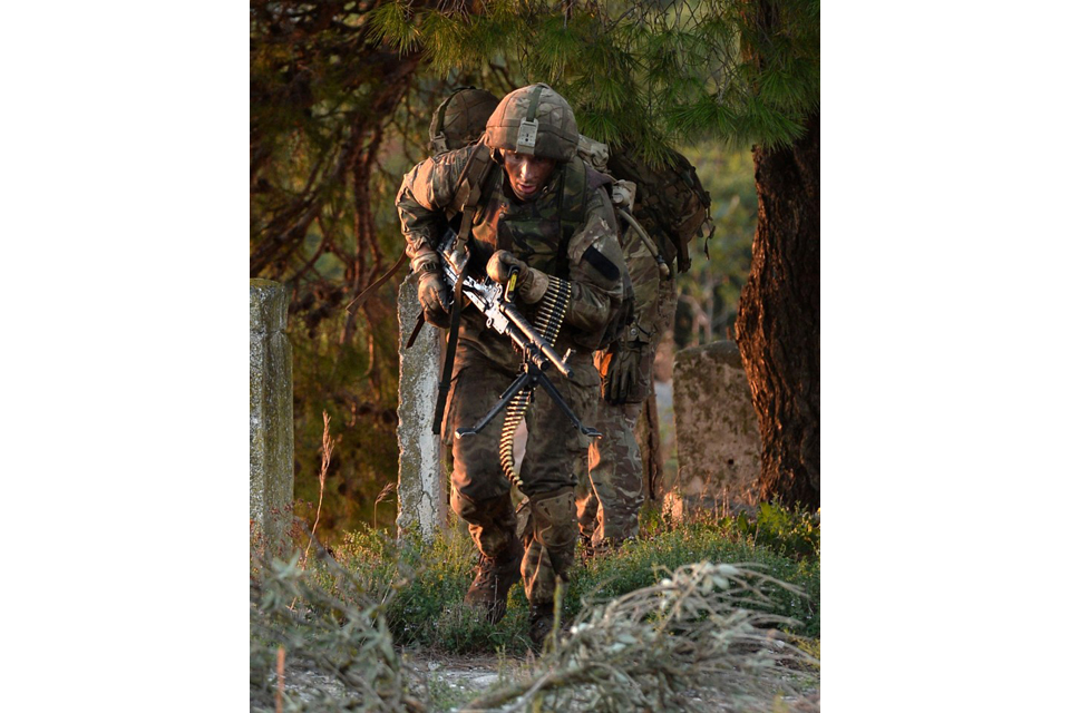 Royal Marines break cover of a wooded area