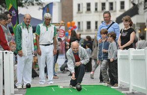 A man plays bowls while several people look on watching