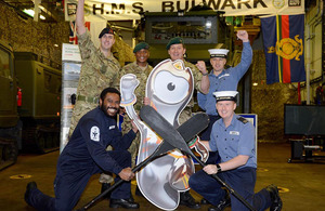 Members of HMS Bulwark's ship's company surround a cut-out of an Olympic mascot to cheer on Senior Service Olympian Lieutenant Pete Reed