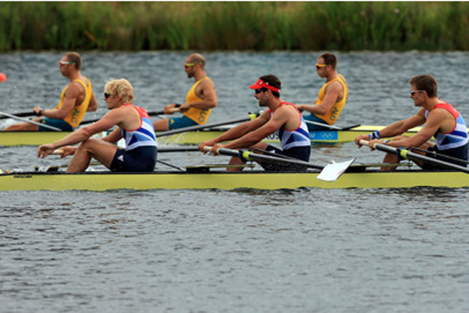 The Team GB Men's Fours team, (left to right) Andrew Triggs Hodge, Tom James, Lieutenant Pete Reed and Alex Gregory, pass the Australian crew to win their semi-final at Eton Dorney Lake near Windsor