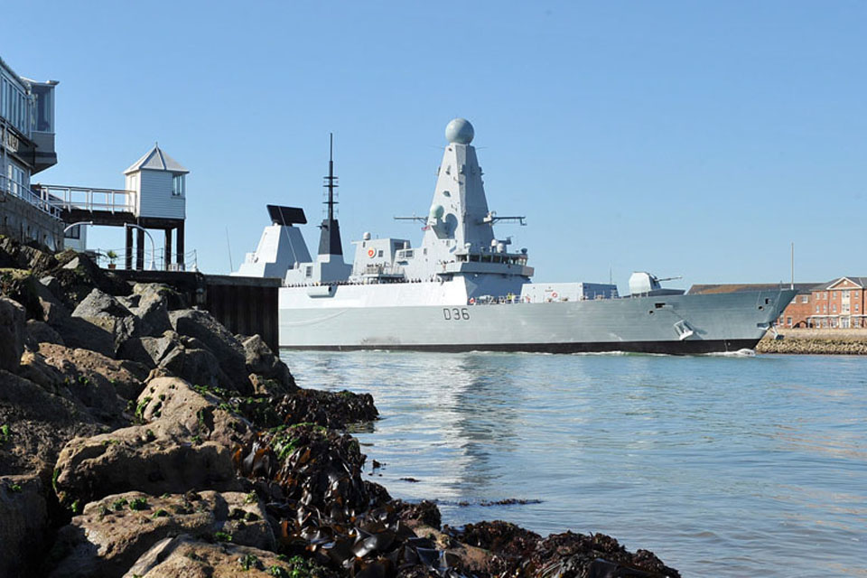 HMS Defender passes between the harbour walls at Portsmouth