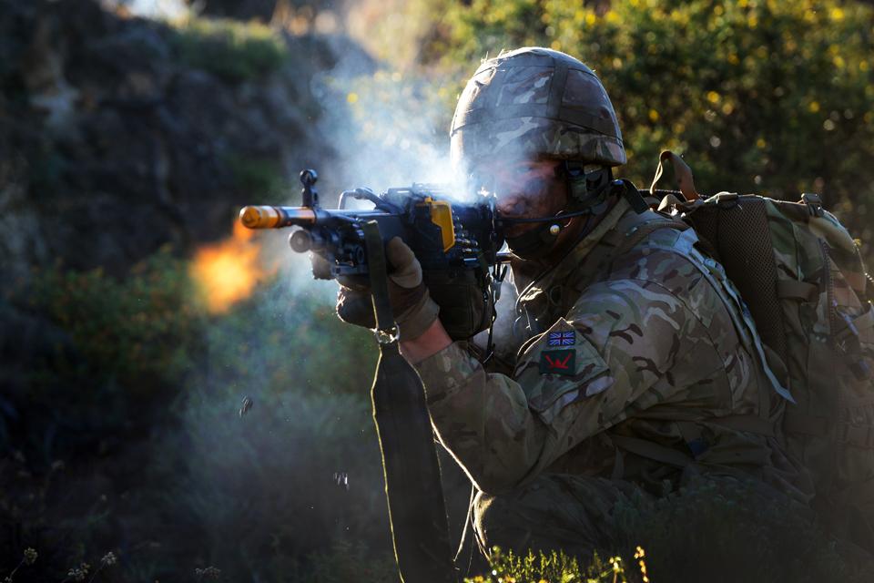 A reservist soldier fires a machine gun