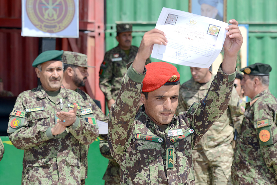 An Afghan soldier proudly displays a certificate