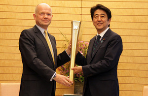 British Foreign Secretary William Hague and Japanese Prime Minister Shinzo Abe hold a London 2012 Olympic torch as a symbol of UK-Japan collaboration.