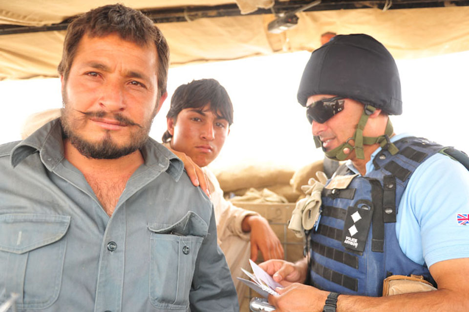 Ministry of Defence Police Inspector Tony Micallef looks in on Afghan Police at Checkpoint Noorzai
