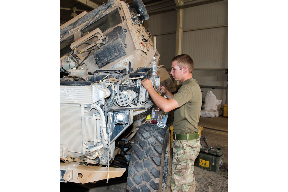 A mechanic works on a Foxhound armoured vehicle