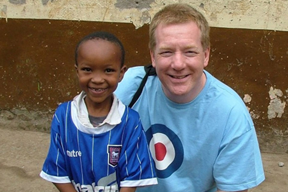 Squadron Leader Neil Hope with a small boy at the Mogra Star Academy in Kenya